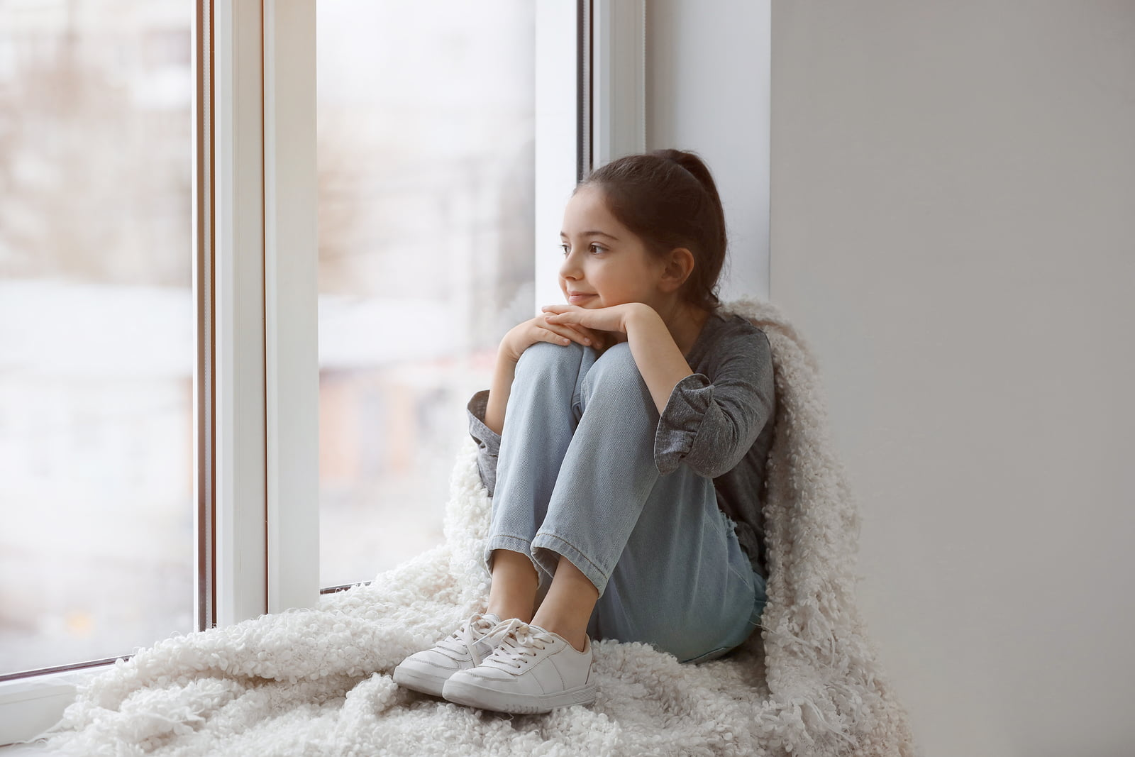A girl snuggled up in a blanket by a window, staring out at the frosty weather.