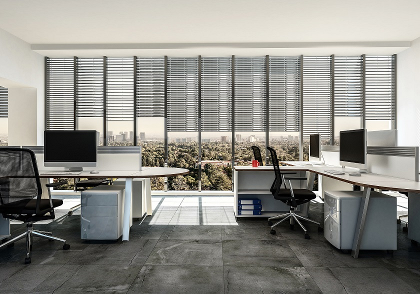 An office setting of a large company, with large windows in the background featuring venetian blinds.