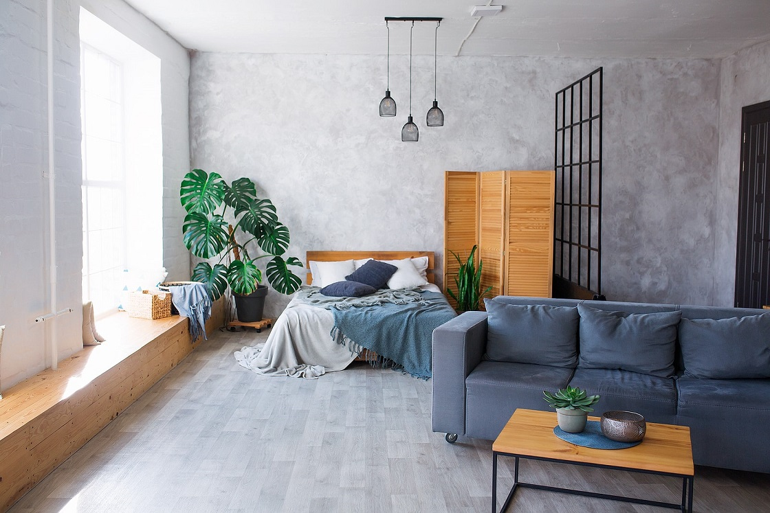 A spacious apartment with a blue couch, bed, and a large window letting in sunlight.