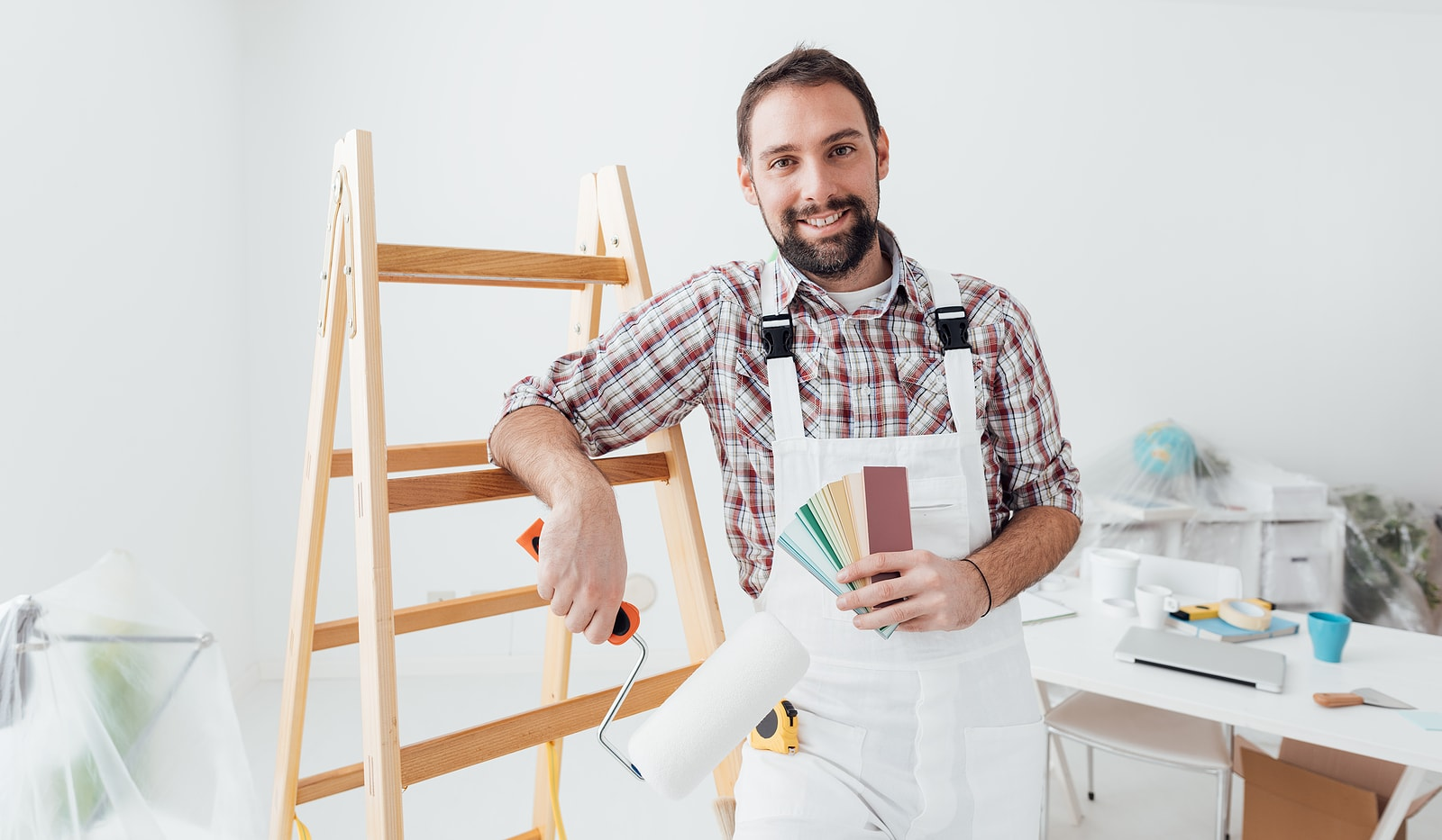 A smiling man standing in front of a white wall. Leaning against a step ladder, holding colour patches and a roller for painting.