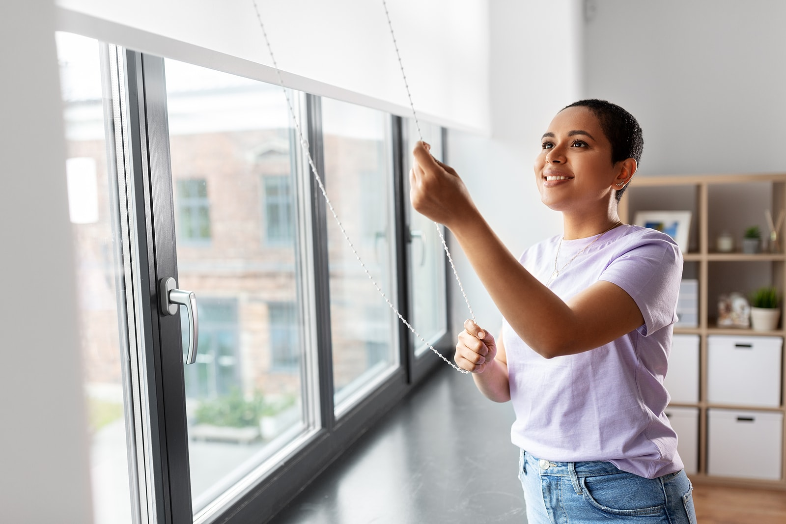 A young woman, smiling as she pulls up her roller blinds.