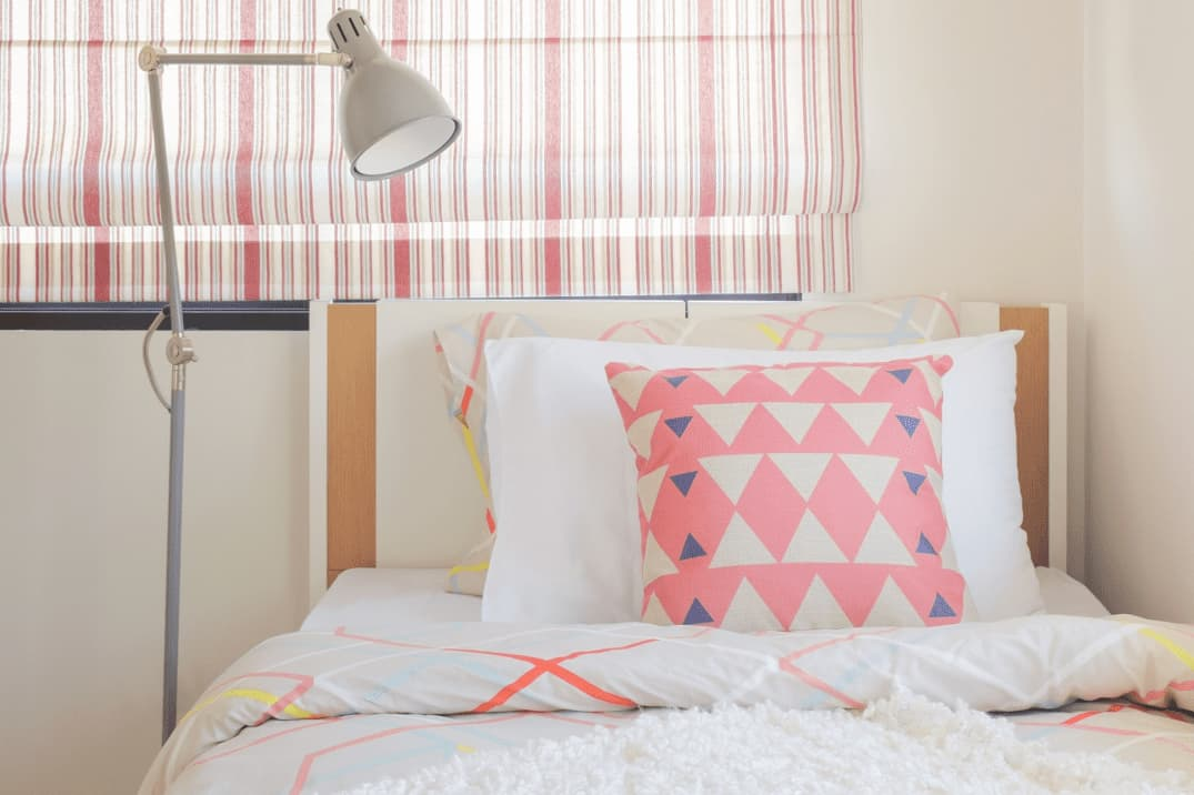 A cosy bedroom featuring pink, blue, and white patterns bedsheets and striped window blinds.