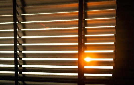 Sun filtering through venetian blinds