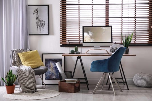 A stylish interior room featuring a set of venetian blinds and some floor length curtains.
