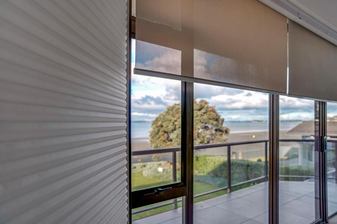 Blinds at a home peaking out into the beach from NZ Blinds