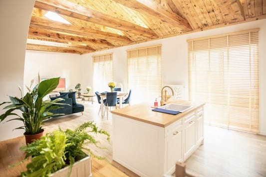Beautiful cosy living room with light island kitchen, wooden blinds and high wooden ceiling