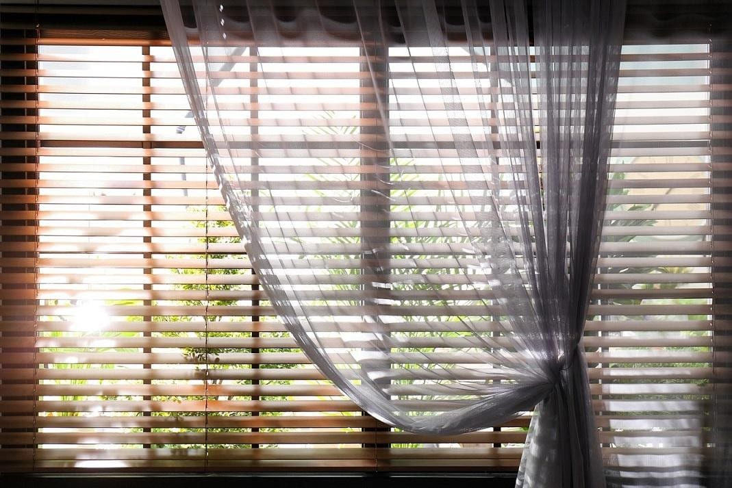 Sunscreen roller blinds with a transparent curtain draped and tied to the right side. Beautiful wooden window blinds with sun shining through.