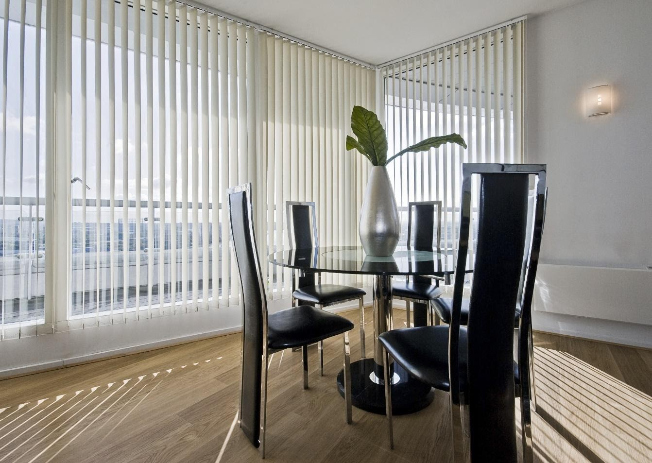 stylish modern dining room with a round glass top table and seats for five with vertical venetian blinds