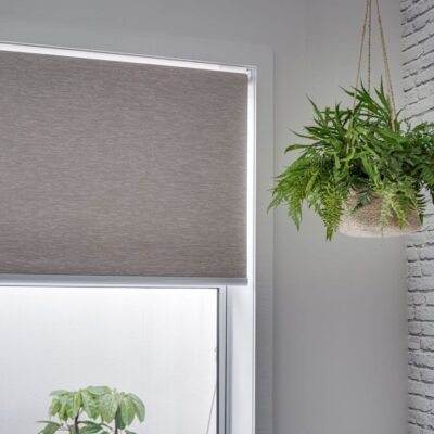 Grey roller blind in front of a plant