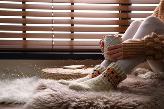 A girl sitting by a window with thermal blinds. Keeping herself warm with a cup of tea, a rug and thermal roller blinds.