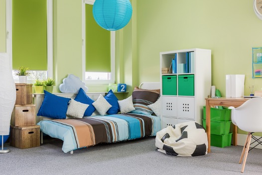 A child's bedroom, featuring stylish pillows, roller blinds, shelving, and a soccer ball beanbag.
