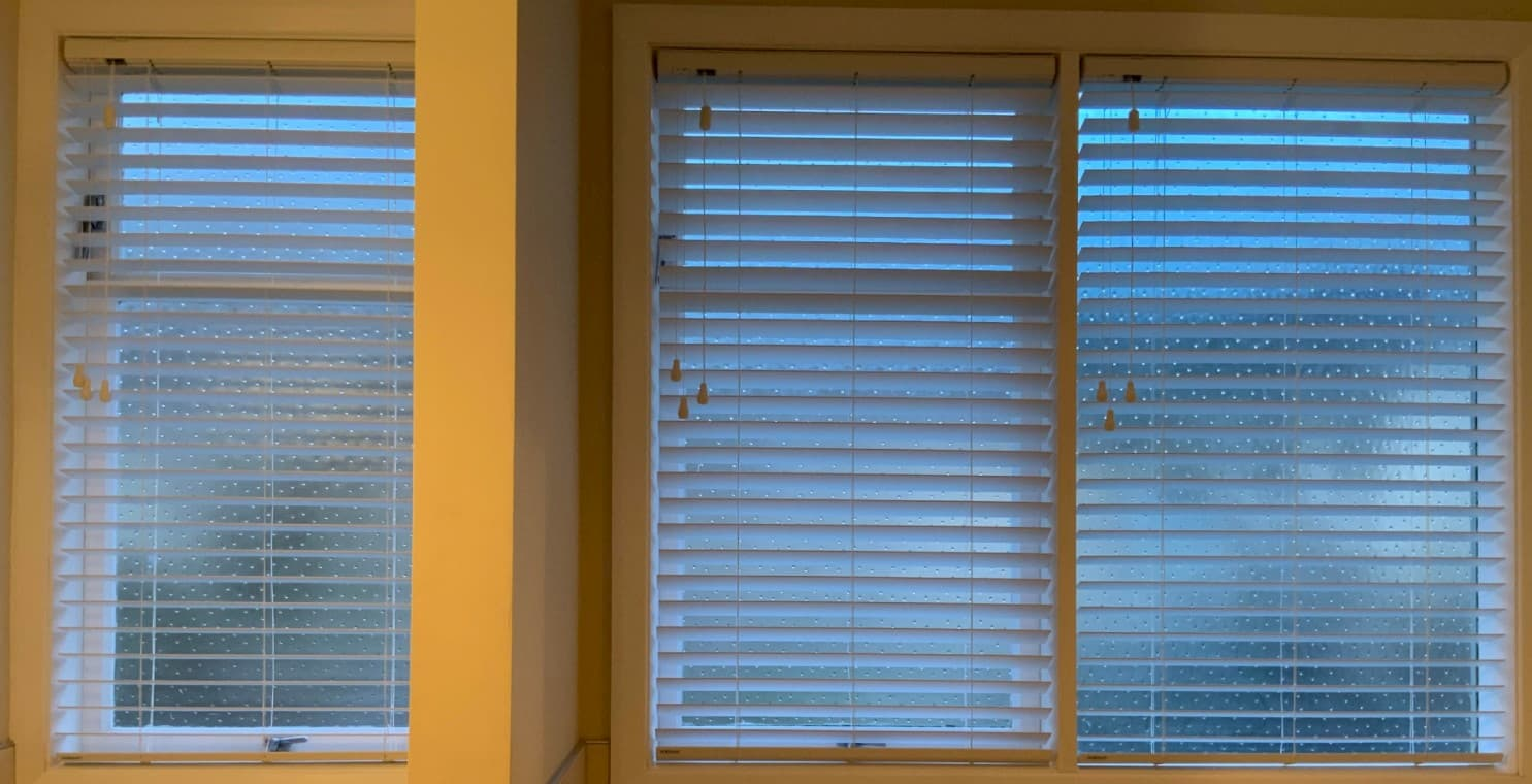 A picture of windows featuring white, corded venetian blinds.