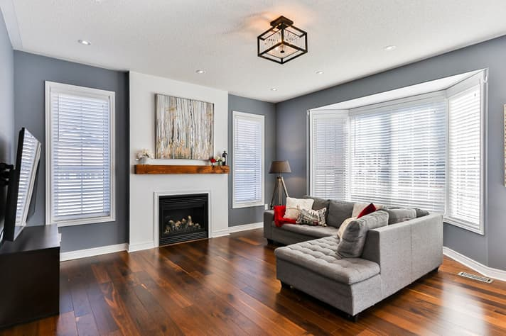 A sleek, stylish living room, featuring a fireplace and large windows covered by venetian window blinds.