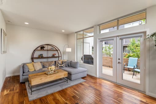 Elegant lounge with wood flooring, angular grey furniture, and grey roller blinds to match.
