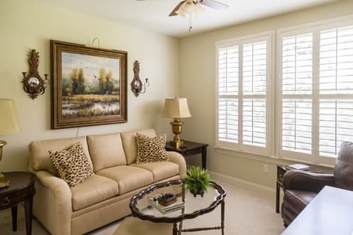 A beautifully furnished lounge space, featuring a brown leather sofa, wall décor, and timeless plantation shutters.