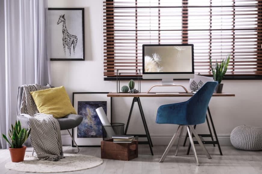 A light and spacious study room with a modern computer desk, featuring large windows, Venetian blinds, pot plants, and artistic décor.