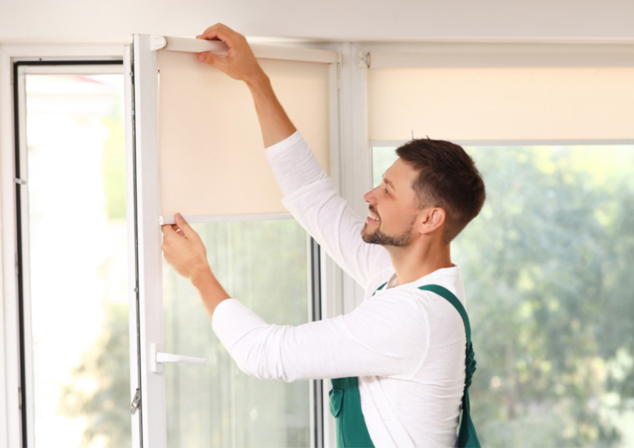 A man standing next to a window, happily installing remote control roller blinds.