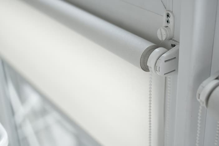 A close-up of fresh white sunscreen roller blinds handed over a glass door.