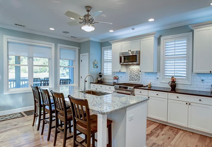 A beautiful kitchen with an island in the middle and sunscreen roller blinds on large windows.