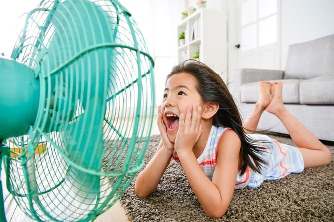 Girl enjoying refreshing breeze from a blue electronic fan