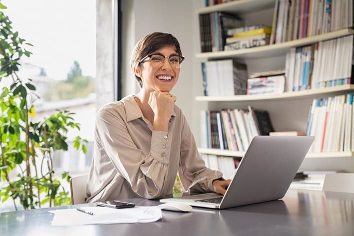 A woman sitting at her desk and smiling, looking up sunscreen roller blind solutions for her home office