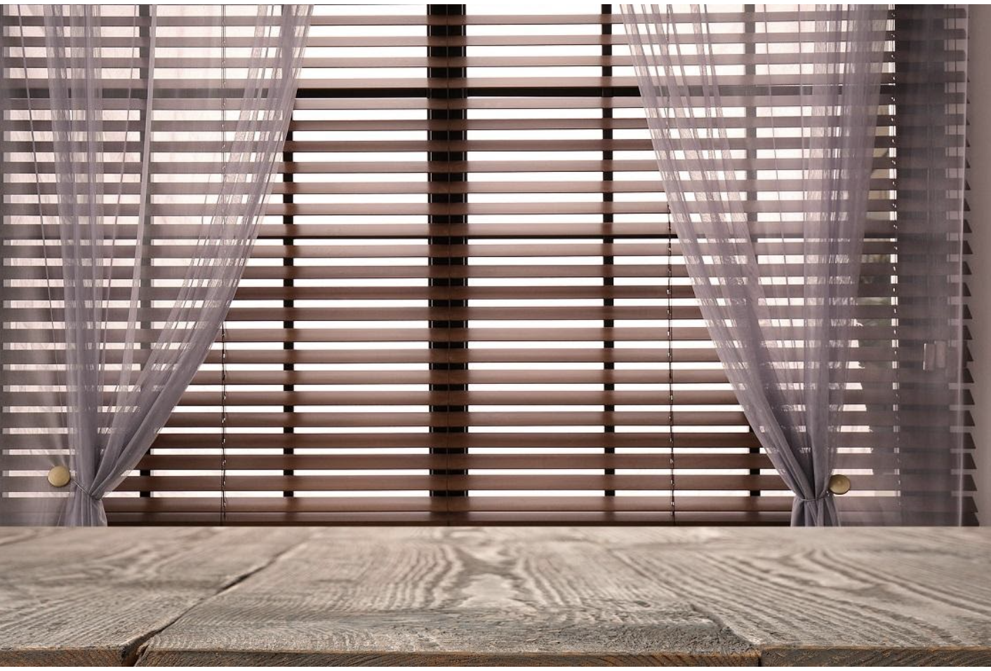 A wooden table in front of a window covered by wooden venetian blinds and sheer curtains.