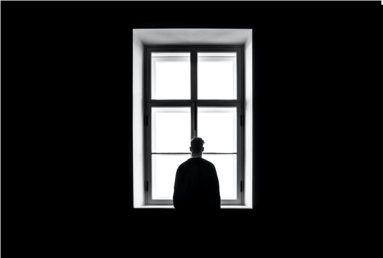 Man standing in dark room in front of bright window