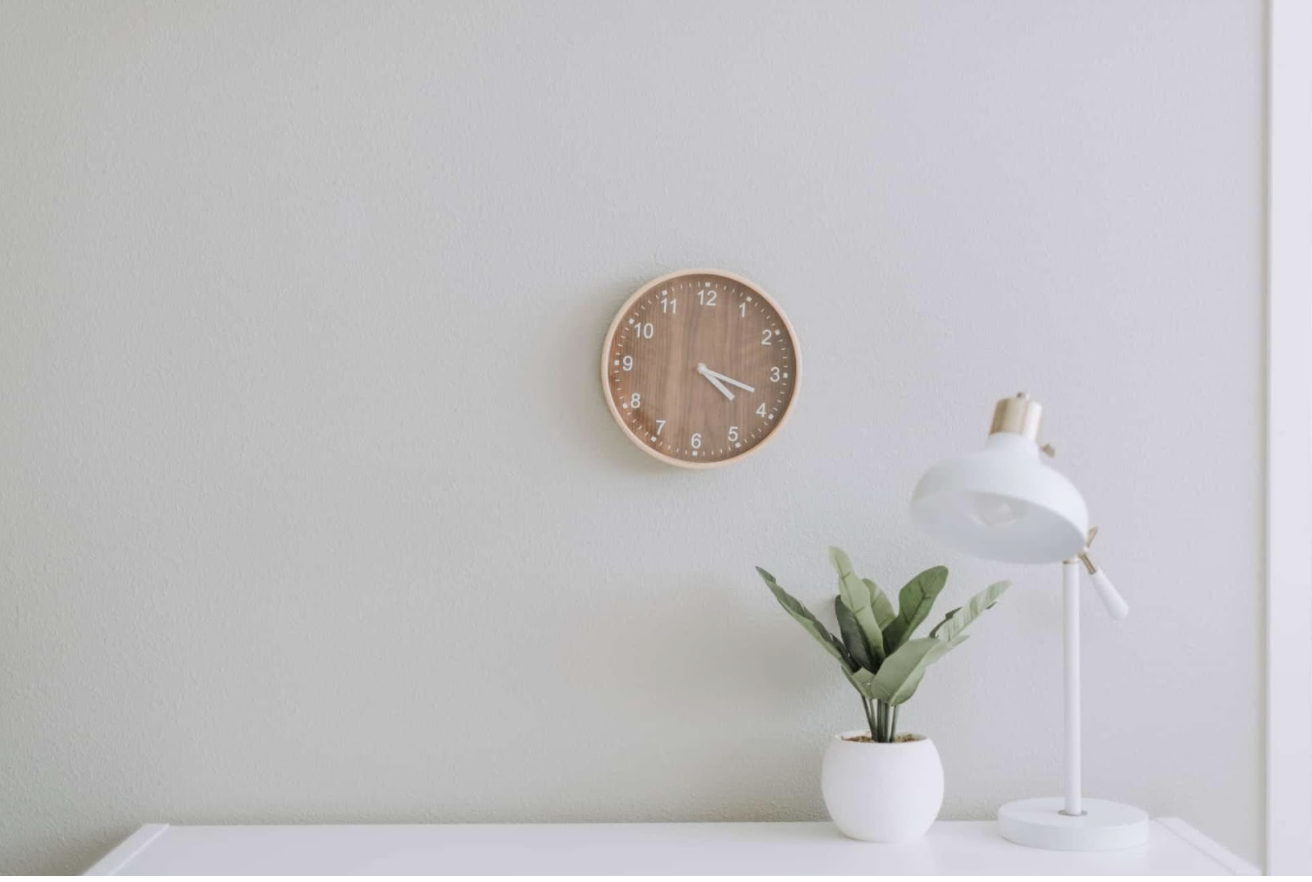 Clock on wall next to modern desk and lamp