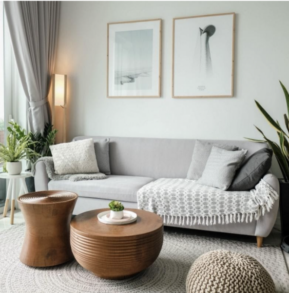 A living room with art on the wall, a white couch, and a coffee table