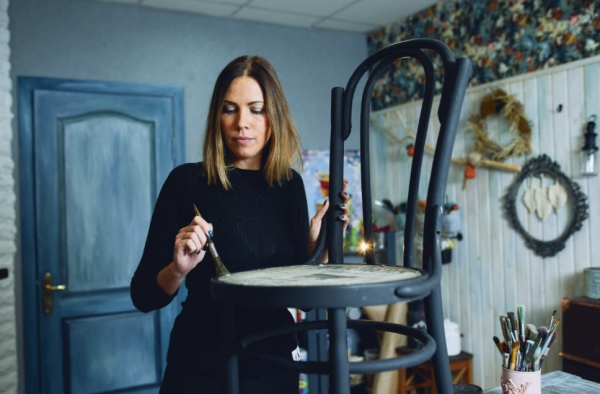 A pretty woman in a blue room, repainting an old chair